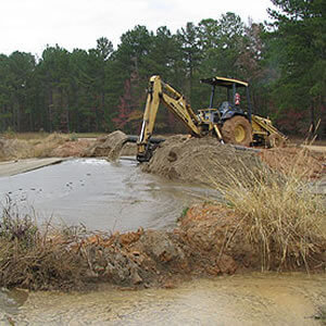 machinery removing sludge from pond